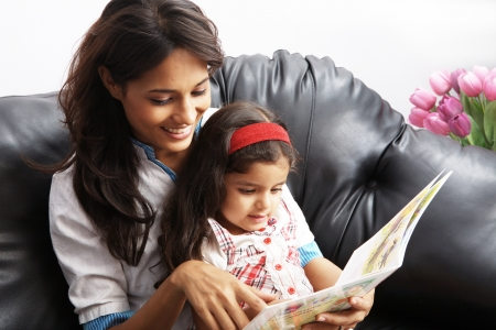 learning to read: Mother with her daughter sitting on a couch and reading a book