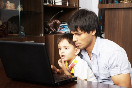 Father and his son using laptop photo
