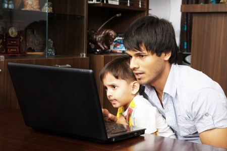 Father and his son using laptop Stock Photo