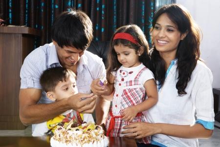 fiesta familiar: Los padres con ni?os que celebran la fiesta de cumplea?os Foto de archivo