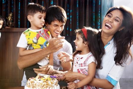 familia comiendo: Los padres con ni?os que celebran la fiesta de cumplea?os Foto de archivo