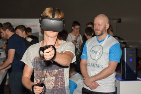 Cologne, Germany - August 24, 2017: A visitor is playing a virtual reality game with oculus rift + touch at the boot of Dell Gaming at Gamescom 2017. Gamescom is a trade fair for video games held annually in Cologne.