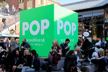 Berlin, Germany - May 3, 2018: Meeting point with visitors outside in the entrance area of re: publica - a big green cube with the imprint POP. re:publica is a conference about Web 2.0, weblogs, social media and the digital society.