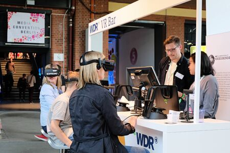 Berlin, Germany - May 3, 2018: Several visitors try Virtual Reality glasses at the WDR radio booth during the re:publica. re:publica is a conference about Web 2.0, weblogs, social media and the digital society.