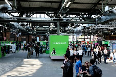 Berlin, Germany - May 3, 2018: View on the entrance hall of re:publica 2018 with visitors and many small booths. re:publica is a conference about Web 2.0, especially weblogs, social media and the digital society.