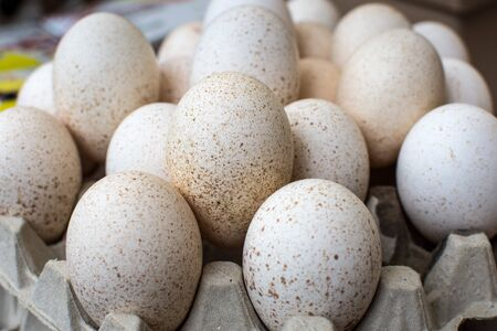 Pile of speckled eggs in carton