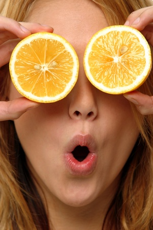 A woman with her mouth rounded using two slices of orange to cover her eyes Stock Photo - 11609203