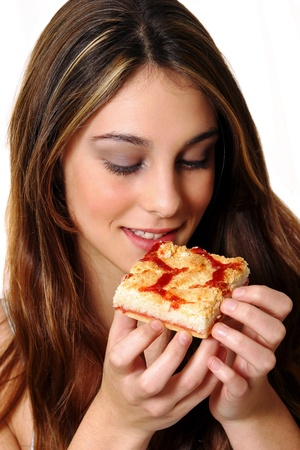 A woman looking at a piece of pizza she is holding Stock Photo - 11609217