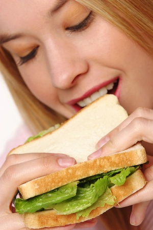 A blonde hair girl eating a sandwich  LANG_EVOIMAGES