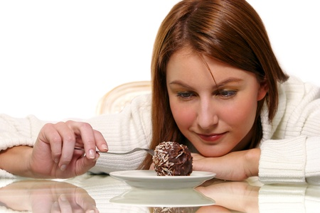 A woman looking down with her chin on her hand while using a fork to poke a chocolate ball cake Stock Photo - 11609237