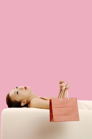 Woman resting on the couch holding paper bag