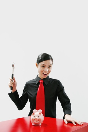 Businesswoman holding hammer with a piggy bank in front of her Stock Photo - 11610002
