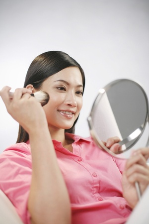 Businesswoman applying make-up Stock Photo - 11610153