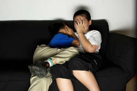Two brothers covering their face while watching a horror movie Stock Photo - 11628509