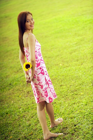 Back shot picture of woman holding a sunflower Stock Photo - 11629078