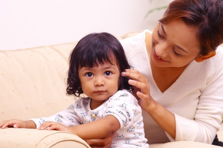 Woman playing with her daughter's hair Stock Photo - 11629477