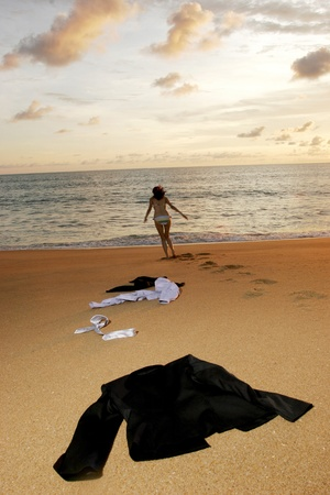 Businesswoman running to the sea leaving her clothes on the beach.