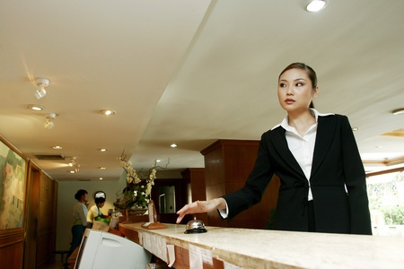 Businesswoman ringing desktop bell at the reception counter. LANG_EVOIMAGES