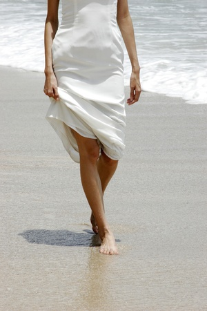 Woman in white walking along the beach. Stock Photo - 11629820