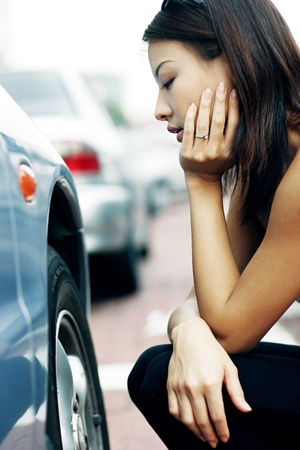 Woman looking at the flat tire with frustration. Stock Photo - 11629824
