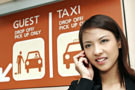 Businesswoman talking on the phone while waiting at the taxi stand. Stock Photo - 11629835