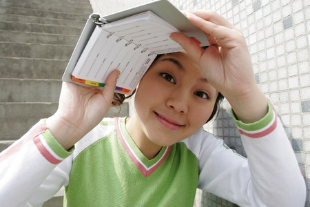Girl shielding her face with an organizer. Stock Photo - 11629842