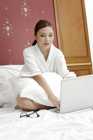 Businesswoman sitting on the bed using laptop. Stock Photo - 11629850