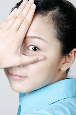 Woman covering eye with her hand. Stock Photo - 11629878