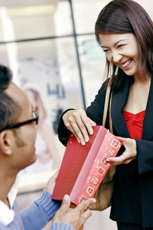 Businesswoman smiling while opening her present.