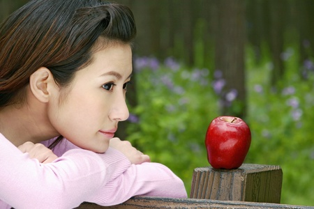 Woman with a red apple beside her. LANG_EVOIMAGES