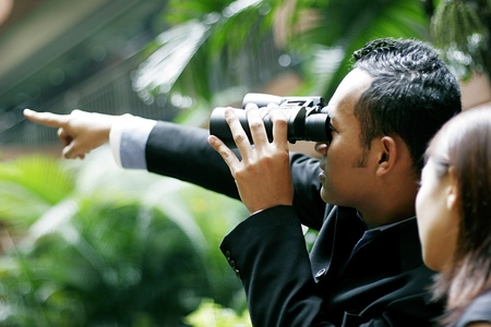 Businessman pointing while using binoculars. Stock Photo - 11630057