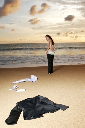Businesswoman discarding her clothes on the beach. Stock Photo - 11630065