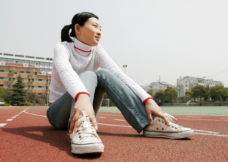 Girl sitting on the sports track. Stock Photo - 11630106