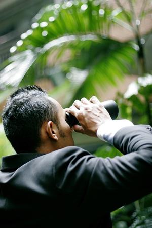 Businessman using binoculars. Stock Photo - 11630132