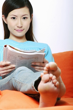 Woman sitting on the couch reading. Stock Photo - 11630135
