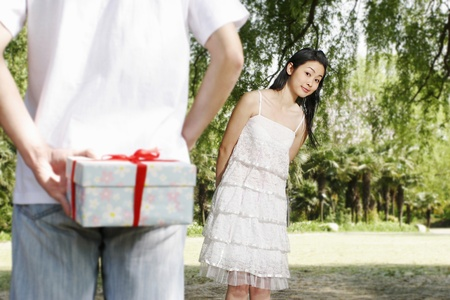 Man hiding a surprise gift from his girlfriend. Stock Photo - 11630157