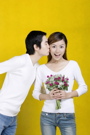 Woman getting a bouquet of flowers and a kiss from her boyfriend. LANG_EVOIMAGES