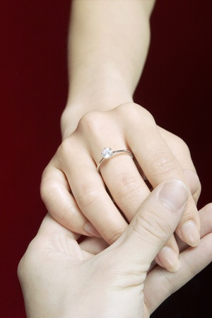 Couple holding hands with woman wearing engagement ring. Stock Photo - 11630187