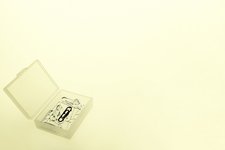 A single black paper clip mixed with a box of white paper clips Stock Photo - 11630237