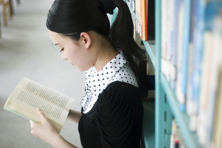 Young woman reading book in the library Stock Photo - 11630447