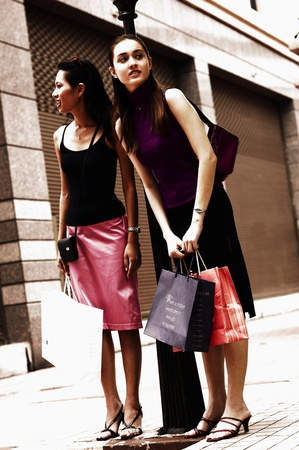 Two friends waiting for a taxi after shopping Stock Photo - 12593656