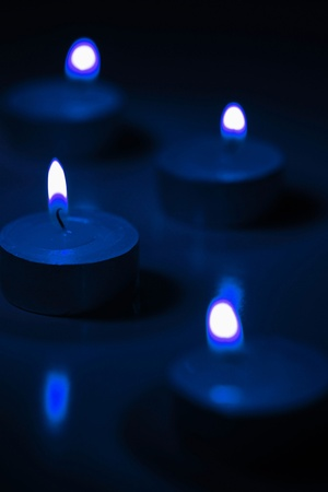 Lit candles glowing in the dark Stock Photo - 12593693
