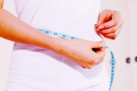 Woman measuring her waist Stock Photo - 12642335