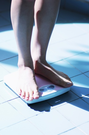 Knee down shot of a woman standing on a weighing machine Stock Photo - 12642349