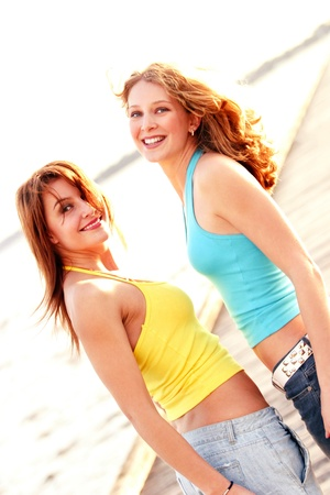 Two women with one wearing yellow and the other wearing blue halter neck standing at the beach Stock Photo - 12642839