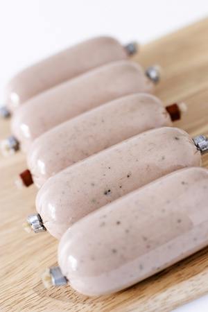 Liver sausages in a row on wooden plate Stock Photo - 12642924