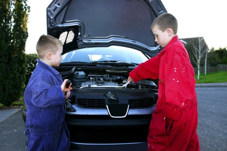 Two boys in mechanic suits repairing the front of a car Stock Photo - 12642962