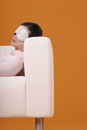 Woman lying on couch, wearing sleep mask Stock Photo - 12643112