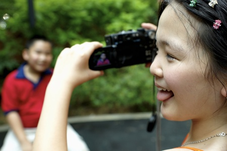 Girl snapping her brother's picture with a digital camera Stock Photo - 12643145