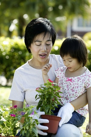 Girl watching her mother doing some gardening work in the park Stock Photo - 12643179